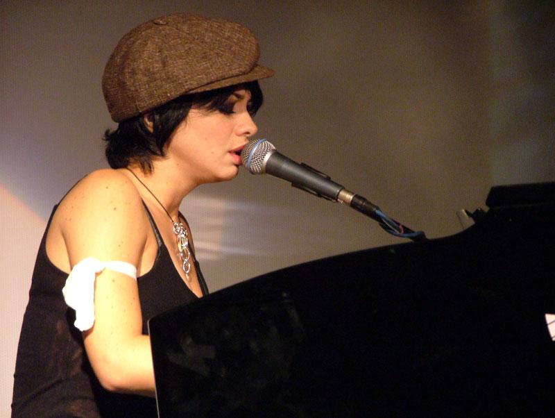 Dolcenera canta al piano durante un concerto. Un cappello marrone le copre in parte i corti capelli neri, al collo porta un ciondolo elaborato e al braccio una fascia bianca che risalta contro il suo vestito nero