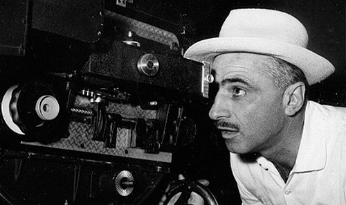 Un giovane Monicelli in camicia e cappello bianco guarda dall'obiettivo di una cinepresa in uno scatto in bianco e nero