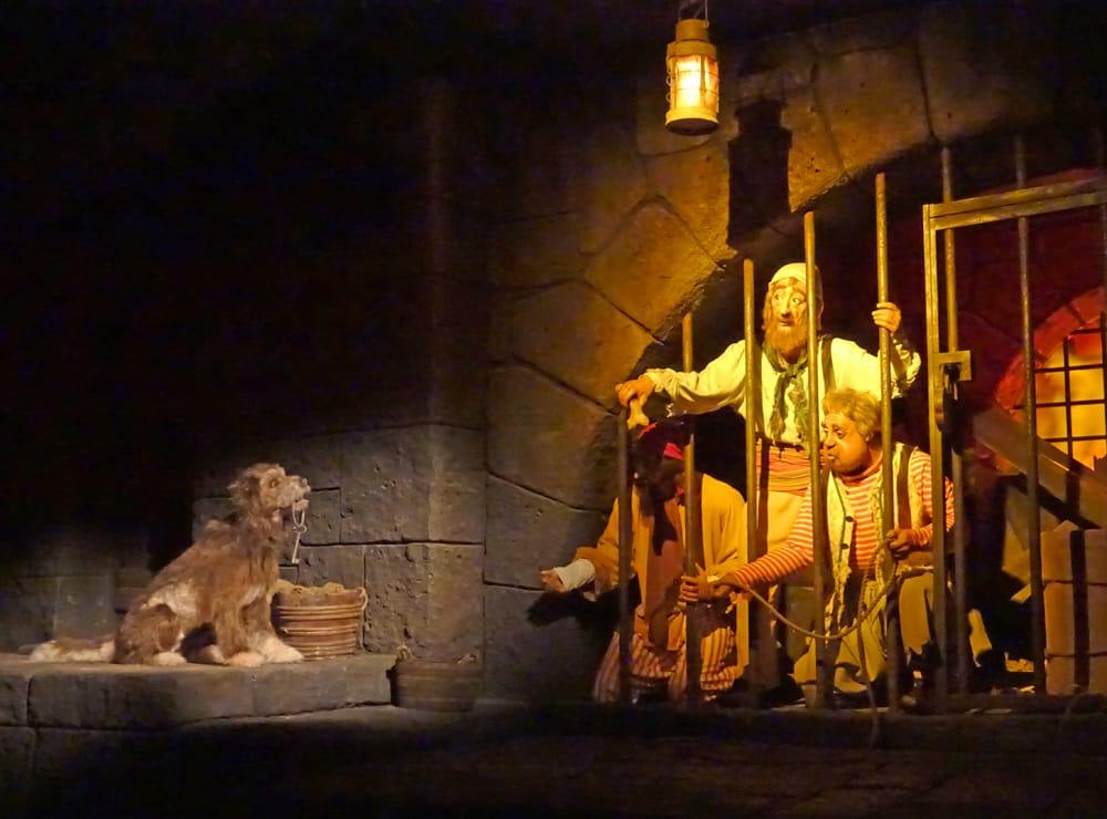 """Foto all'interno della giostra """"Pirati dei Caraibi"""" in cui i pirati cercano di attirare il cane per farsi portare le chiavi della prigione."""
