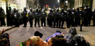 Due manifestanti scambiano un bacio davanti alla fila di polizia antisommossa, durante le proteste a Bristol